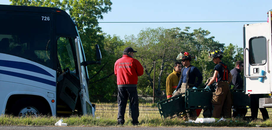 Firefighters clean up where a bus (left) was involved in an accident with an SUV and a construction truck on southbound Interstate 35 near the Luckey Road exit about 8 a.m. Friday. Photo: John Davenport / San Antonio Express-News