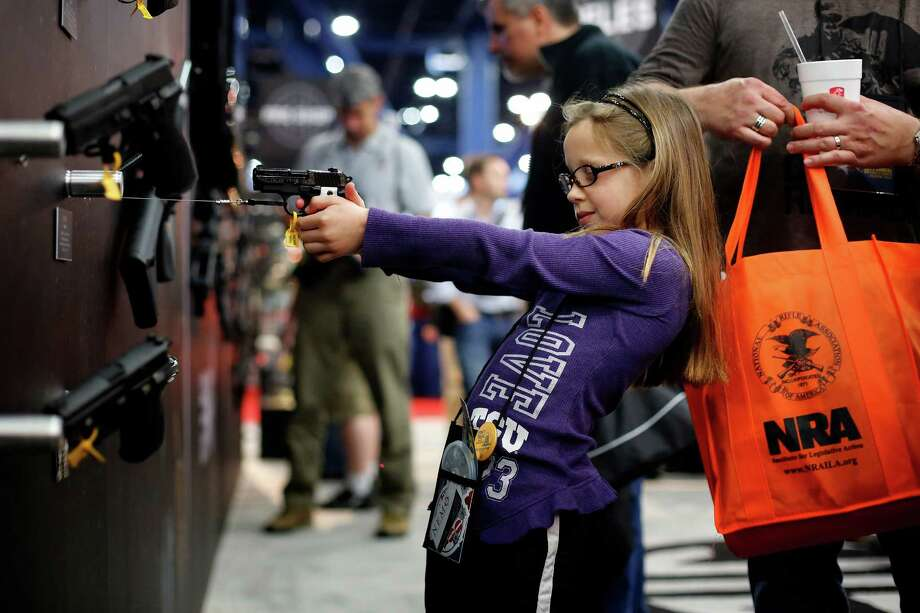 Sydney Morgan, 7, inspects a Sig Sauer pistol during Friday's opening of the 142nd NRA Annual Meetings and Exhibits at the George R. Brown Convention Center downtown. Some 70,000 members are expected to attend. Photo: Â TODD SPOTH, 2013 / © TODD SPOTH, 2013
