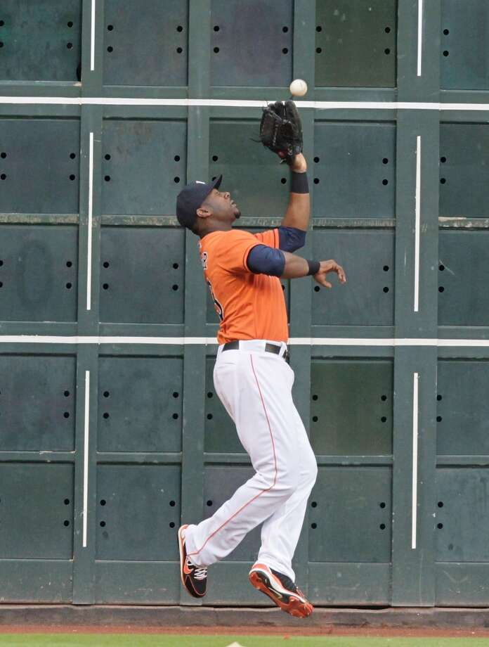 Chris Carter of the Astros makes a catch at the wall against the Tigers.