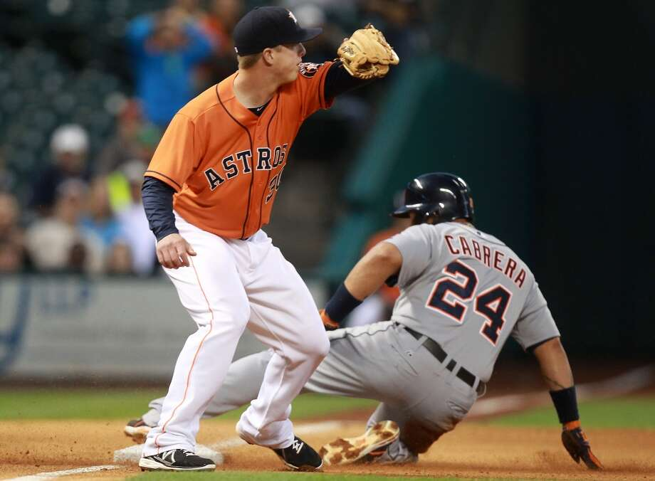 Miguel Cabrera of the Tigers slides into third base before Matt Dominguez of the Astros can tag him.