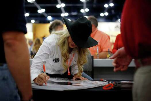 A model for Taurus firearms signs posters for attendees, during day 1 of the 142nd NRA annual meetings and exhibits, Friday, May 3, 2013 at the George R Brown convention center in  (TODD SPOTH FOR THE CHRONICLE) Photo: © TODD SPOTH, 2013 / © TODD SPOTH, 2013