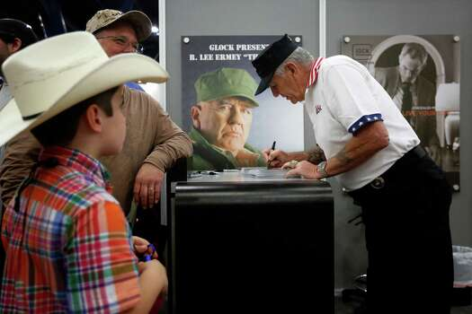 """The Gunny"", R. Lee Ermey signs a poster for 7-year-old Blaine Simpson, during day 1 of the 142nd NRA annual meetings and exhibits, Friday, May 3, 2013 at the George R Brown convention center in  (TODD SPOTH FOR THE CHRONICLE) Photo: © TODD SPOTH, 2013 / © TODD SPOTH, 2013"