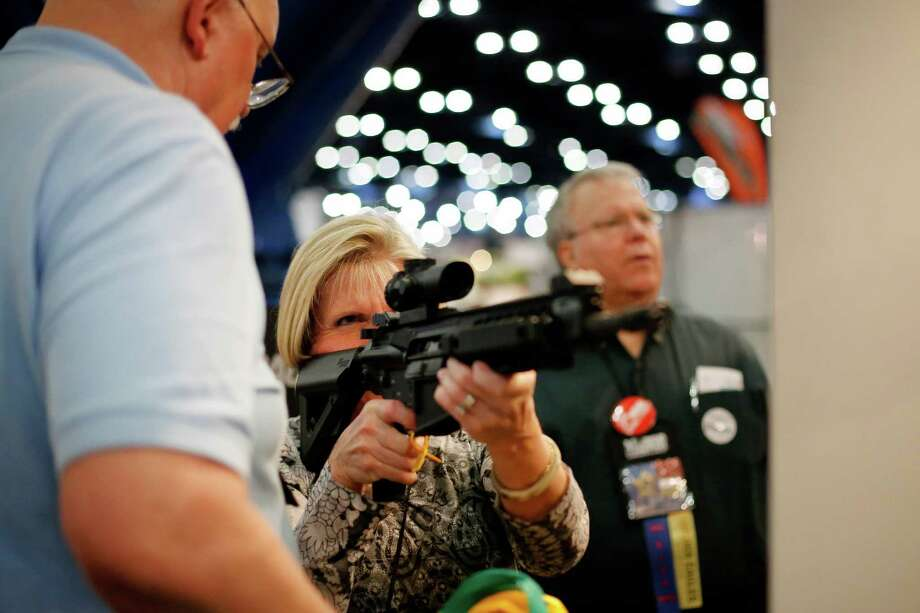 An expo attendee inspects a Sig Sauer rifle, during day 1 of the 142nd NRA annual meetings and exhibits, Friday, May 3, 2013 at the George R Brown convention center in  (TODD SPOTH FOR THE CHRONICLE) Photo: © TODD SPOTH, 2013 / © TODD SPOTH, 2013