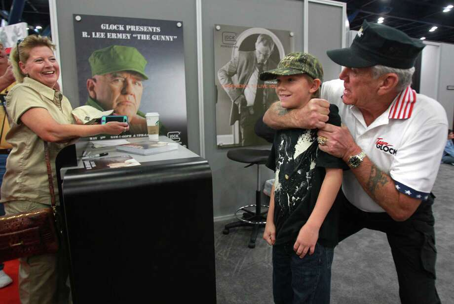 "Terri Hoyt smiles as while son Ryan Hoyt, 11, is in a headlock by R. Lee Ermey ""The Gunny"" on the exhibition floor during the National Rifle Association Convention at George R. Brown on Friday, May 3, 2013, in Houston. Photo: Mayra Beltran / © 2013 Houston Chronicle"