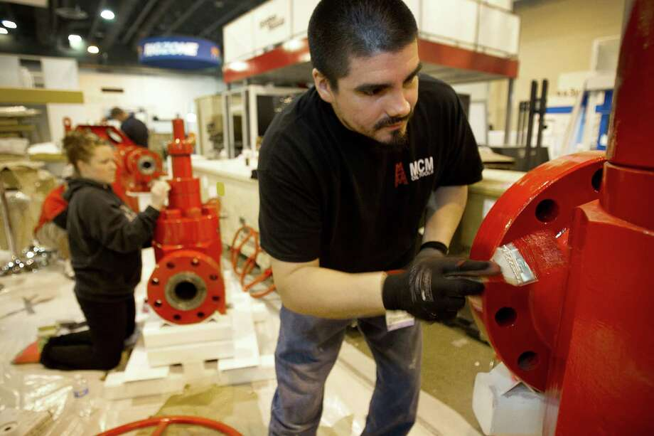 Jaime Mena touches up the MCM Oil Tools booth for the Offshore Technology Conference, which that starts next week. Photo: Brett Coomer, Staff / © 2013 Houston Chronicle
