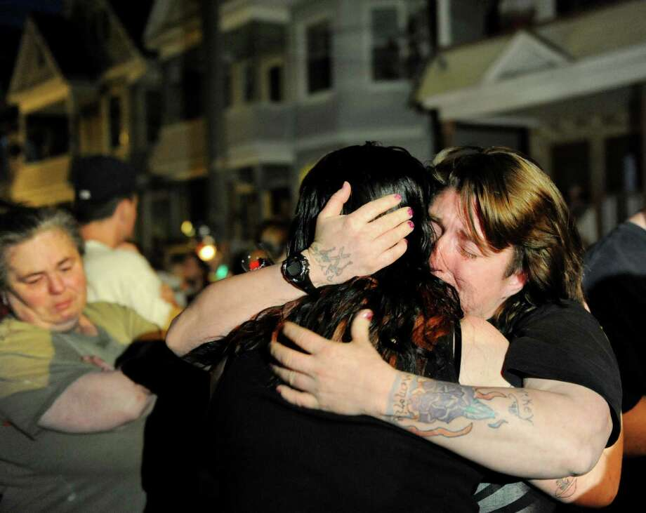 "Christine Kilcher, right, embrace her grief-stricken friend, Jennica Duell, center, on Friday, May 3, 2013, in Schenectady, N.Y. Duell's three children and their father perished in a fire Thursday night. ""I lived every day for those kids,"" she said. (Cindy Schultz / Times Union) Photo: Cindy Schultz / 10022277A"