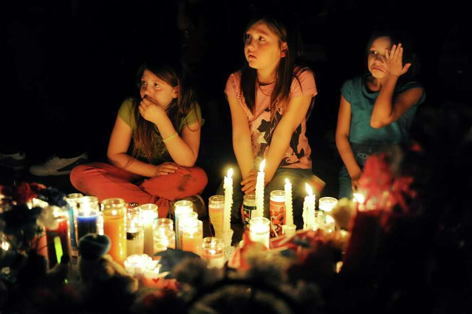 Cousins Kirsten Gauvreau, 9, left, Haili Clark, 9, center, and Mischa Richard, 8, cry as they sit by a memorial to their perished family members on Friday, May 3, 2013, in Schenectady, N.Y. Dave Terry and his three children died in a fire Thursday night. (Cindy Schultz / Times Union) Photo: Cindy Schultz / 10022277A