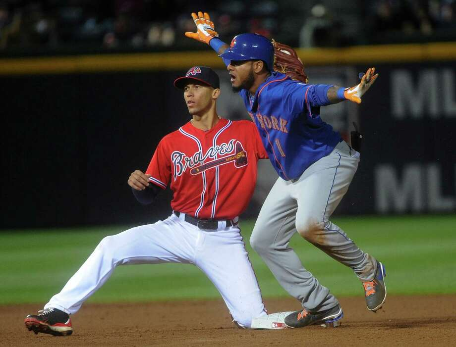 New York Mets center fielder Jordany Valdespin (1) makes a safe sign as he and Atlanta Braves shortstop Andrelton Simmons (19) look to the umpire after he steals second base during the tenth inning of a baseball game, Friday, May 3, 2013, in Atlanta. Valdespin was safe on the play. (AP Photo/John Amis) Photo: John Amis