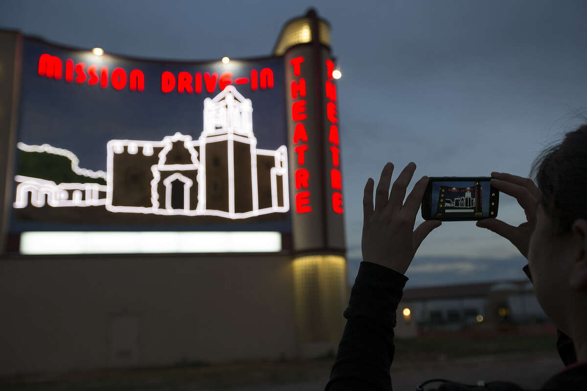 Dina Zavala, who worked on the revitalization of the former drive-in theater, takes a picture of her handiwork.