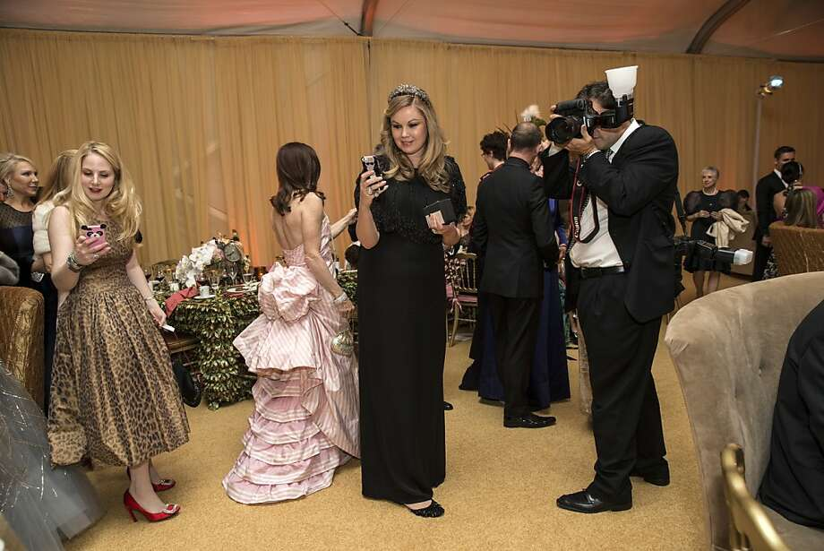 Tatiana Sorokko (center) snaps a photo of a friend while society photographer Drew Altizer (right) captures the moment as well during San Francisco Ballet's Cinderella Opening Night Ball in a tent outside War Memorial Opera House in San Francisco, Calif., on Friday, May 3, 2013.  The party celebrated the opening night and United States premiere of choreographer Christopher Wheeldon's production of Cinderella. Photo: Laura Morton, Special To The Chronicle