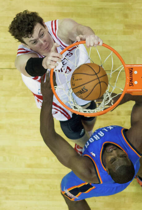 Rockets center Omer Asik, left, jams one home before Thunder power forward Serge Ibaka can do anything about it Friday night at Toyota Center. Photo: Smiley N. Pool, Staff / © 2013  Houston Chronicle