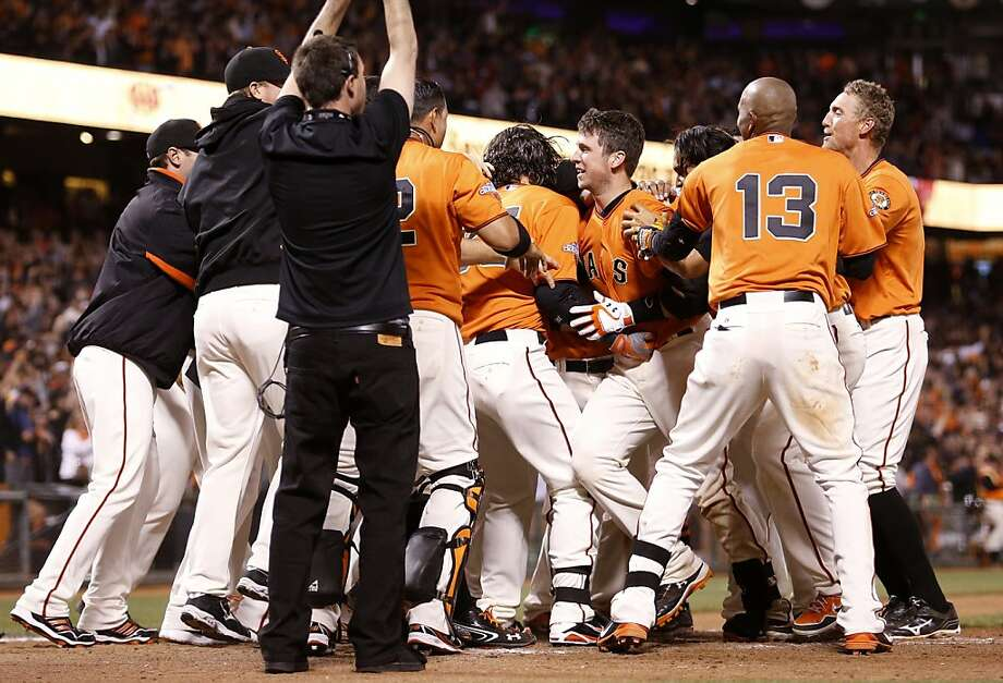 Buster Posey (right center) is the man of the hour as he's greeted at home plate after his winning homer to left. Photo: Beck Diefenbach, Special To The Chronicle