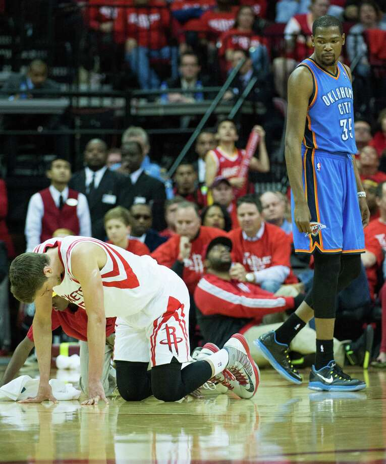 Rockets forward Chandler Parsons is slow to get up after a collision with Oklahoma City's Kevin Durant, right, during the first half of the Thunder's Game 6 win Friday night at Toyota Center. Durant had 27 points as the Thunder advanced to the second round of the playoffs. Game recap: page C3 Photo: Smiley N. Pool, Staff / © 2013  Houston Chronicle