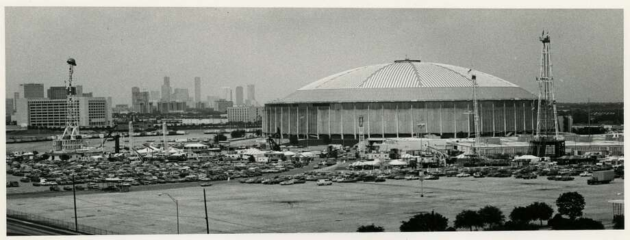 1982 - Equipment is set up around the Astrodome in preparation for the 14th annual Offshore Technology Conference to be held May 1982 - The Offshore Technology Conference exhibits included the two largest displays ever erected in that area: the 172-foot Oilfield Industrial Lines Inc. rig, at the left, topped with a giant hard hat, and the Ideco rig with a 142-foot mast seen at right. Photo: Sandra Shriver, Houston Chronicle
