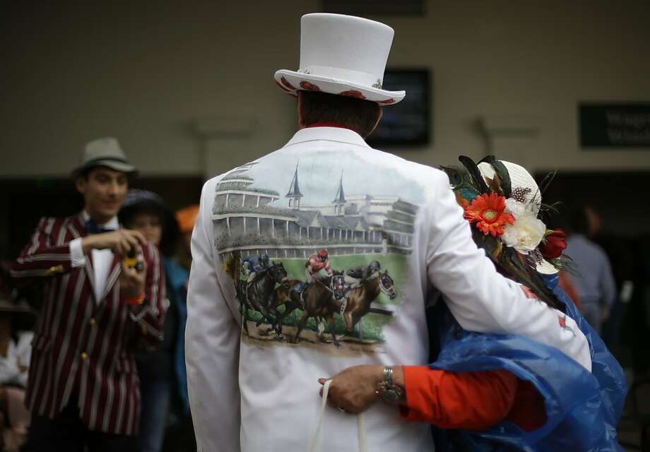 James Cowherd, center, from Las Vegas, Nev., poses for photos with other spectators before the running of the 139th Kentucky Derby at Churchill Downs Saturday, May 4, 2013, in Louisville, Ky. (AP Photo/David Goldman) Photo: David Goldman, Associated Press