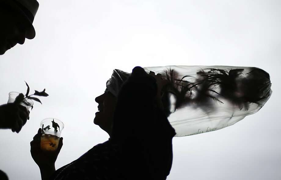 Desirae Masterson, from Indianapolis, Ind., with her hat covered in a plastic bag to protect it from the rain, shares a mint julep with her husband Ray before the running of the 139th Kentucky Derby at Churchill Downs Saturday, May 4, 2013, in Louisville, Ky. (AP Photo/David Goldman) Photo: David Goldman, Associated Press