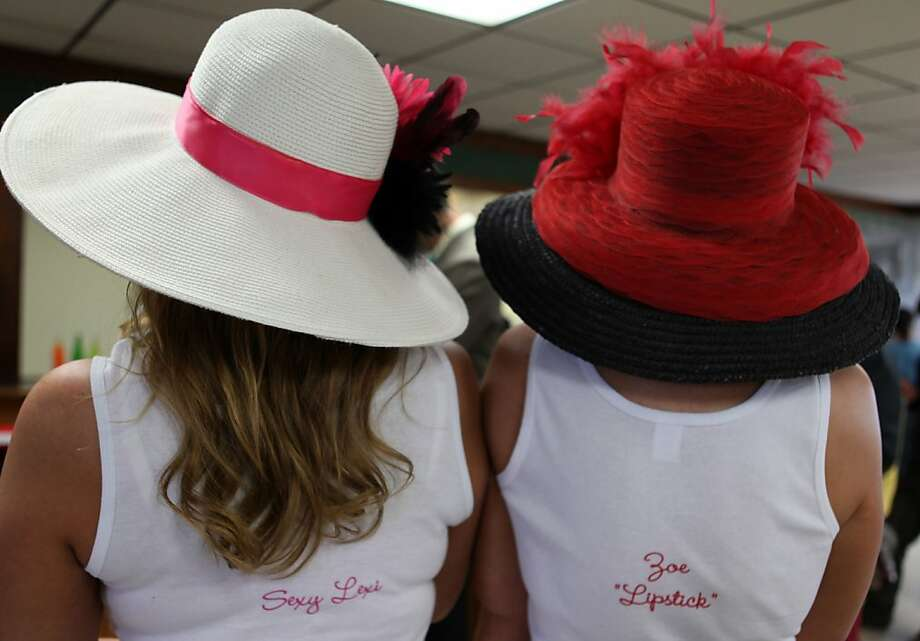Racing fans with hats, 'Sexy Lexi' and 'Zoe Lipstick' are seen in the track kitchen on the morning of the Kentucky Derby at Churchill Downs Saturday, May 4, 2013, in Louisville, Ky.  Today is the 139th running of the Kentucky Derby. (AP Photo/Gregory Payan) Photo: Gregory Payan, Associated Press