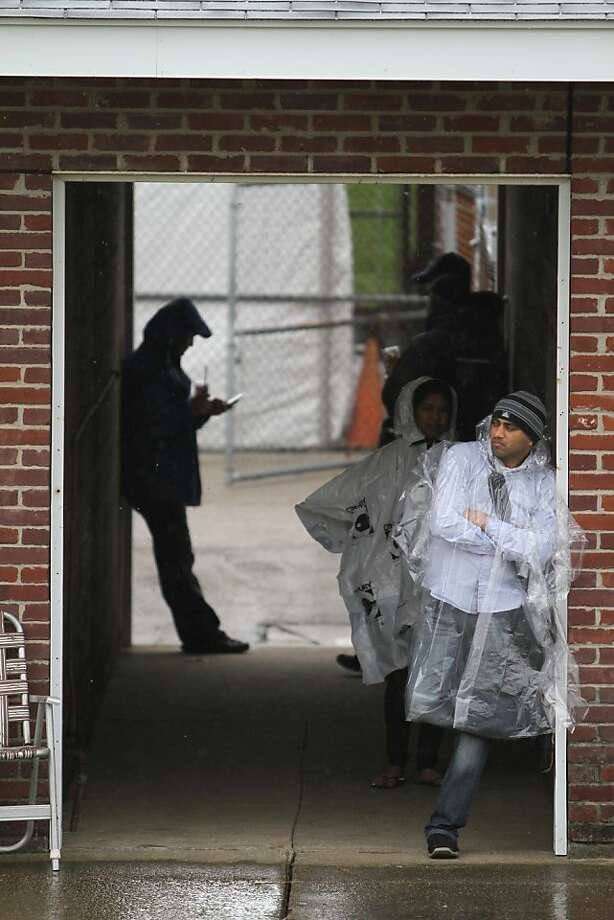Fans take cover from the rain on the morning of the running of the 139th Kentucky Derby at Churchill Downs Saturday, May 4, 2013, in Louisville, Ky. (AP Photo/Julia Weeks) Photo: Julia Weeks, Associated Press