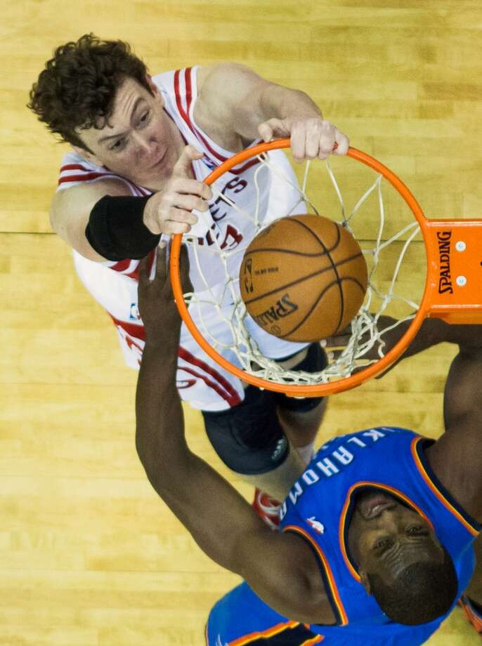 Rockets center Omer Asik, left, jams one home before Thunder power forward Serge Ibaka can do anything about it Friday night at Toyota Center. Photo: Smiley N. Pool, Houston Chronicle