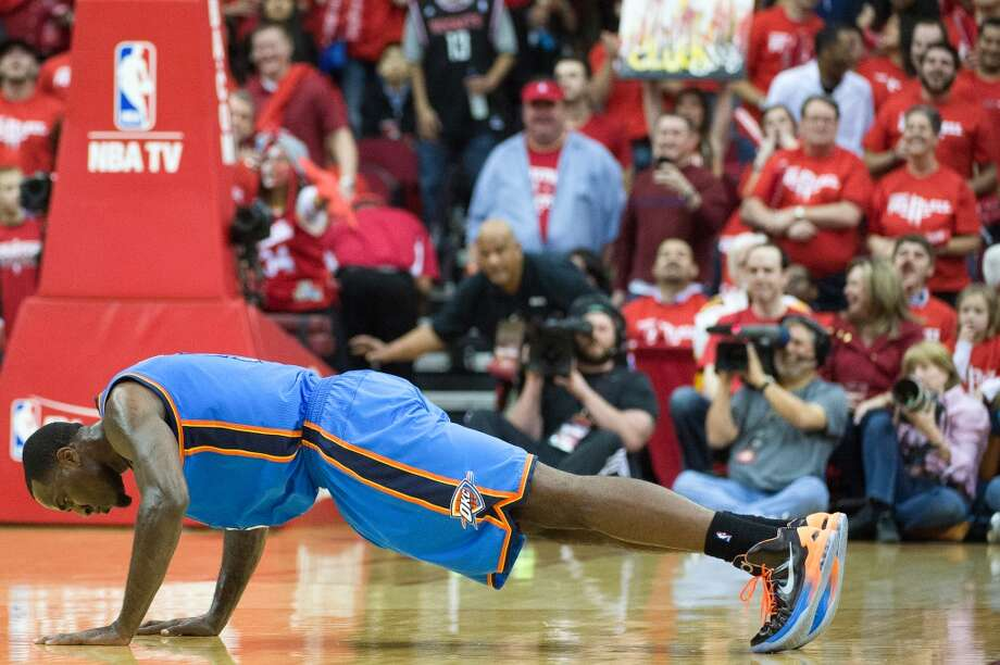 Kendrick Perkins hits the floor for five pushups after he and the Rockets' Francisco Garcia were called for a double technical after tangling in the first half. Photo: Smiley N. Pool, Houston Chronicle