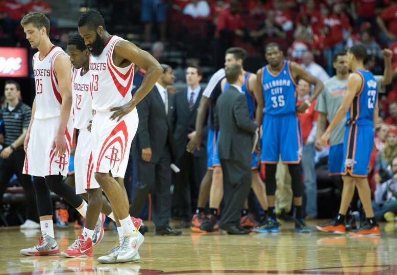 Chandler Parsons (25), Patrick Beverley (12) and James Harden (13) leave the court during timeout du