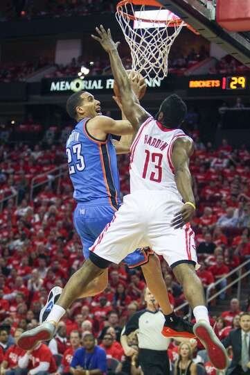 Thunder guard Kevin Martin drives to the basket as Houston Rockets guard James Harden defend.