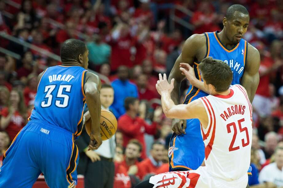 Rockets forward Chandler Parsons is knocked to the floor by a pick from Thunder power forward Serge Ibaka to free Kevin Durant. Photo: Smiley N. Pool, Houston Chronicle