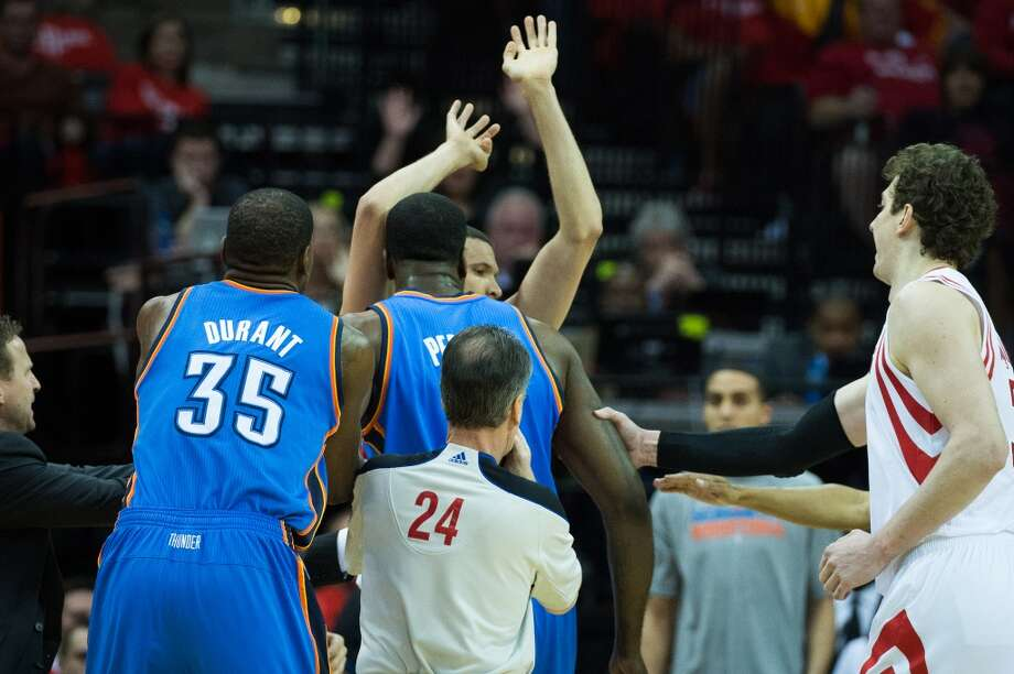 Thunder head coach Scott Brooks, small forward Kevin Durant (35), referee Mike Callahan (24) and Rockets center Omer Asik (3) rush in to separate Thunder center Kendrick Perkins from Rockets guard Francisco Garcia. Photo: Smiley N. Pool, Houston Chronicle