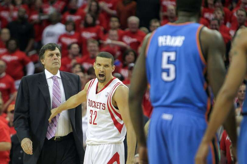 Rockets head coach Kevin McHale  is held back by the Francisco Garcia as  Thunder center Kendrick Pe