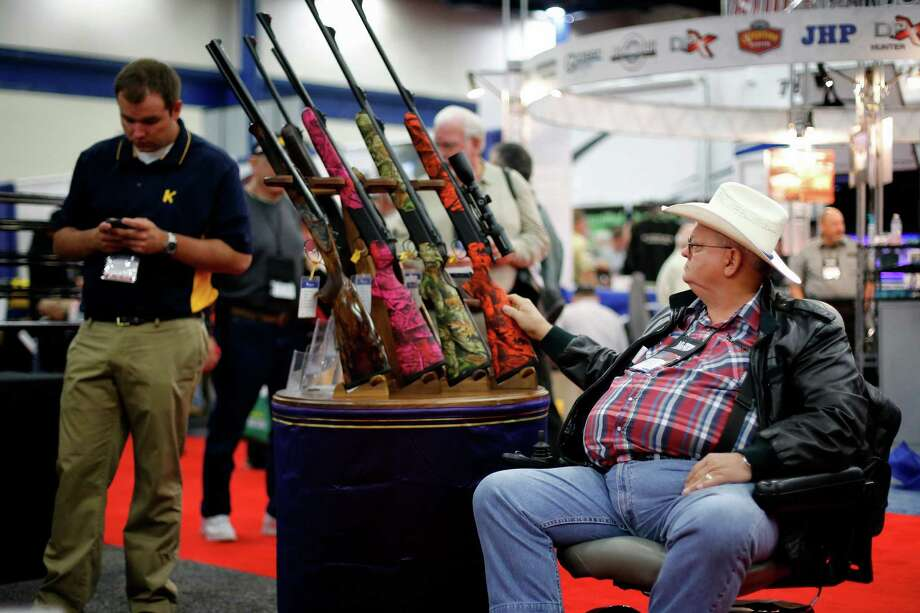 An expo attendee inspects a set of rifles, during day 1 of the 142nd NRA annual meetings and exhibits, Friday, May 3, 2013 at the George R Brown convention center in  (TODD SPOTH FOR THE CHRONICLE) Photo: © TODD SPOTH, 2013 / © TODD SPOTH, 2013