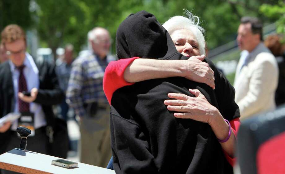 Patricia Maisch, 64, survivor of Tuscon shooting embraces Heather Ross, 27, of No More Names, during a vigil where demonstrators took turns reading the 4,000 names of victims who died last year outside. The small group stood outside the National Rifle Association Convention at George R. Brown on Friday, May 3, 2013, in Houston. Photo: Mayra Beltran / © 2013 Houston Chronicle
