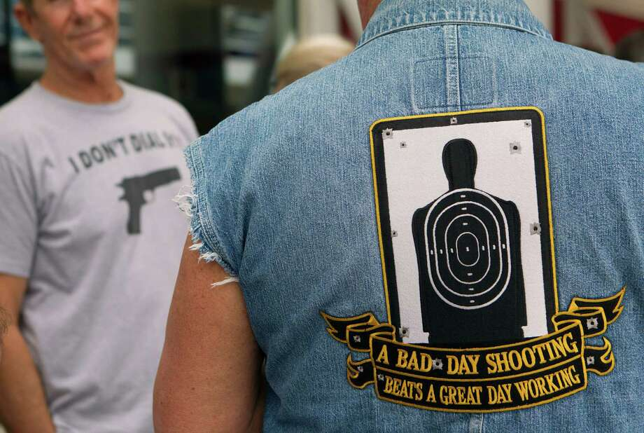 NRA attendee, Rob Heagy, right, of San Francisco, Calif., waits in line outside the George R. Brown Convention Center before the opening of the National Rifle Association's 142 Annual Meetings and Exhibits at the George R. Brown Convention Center Thursday, May 2, 2013, in Houston. 