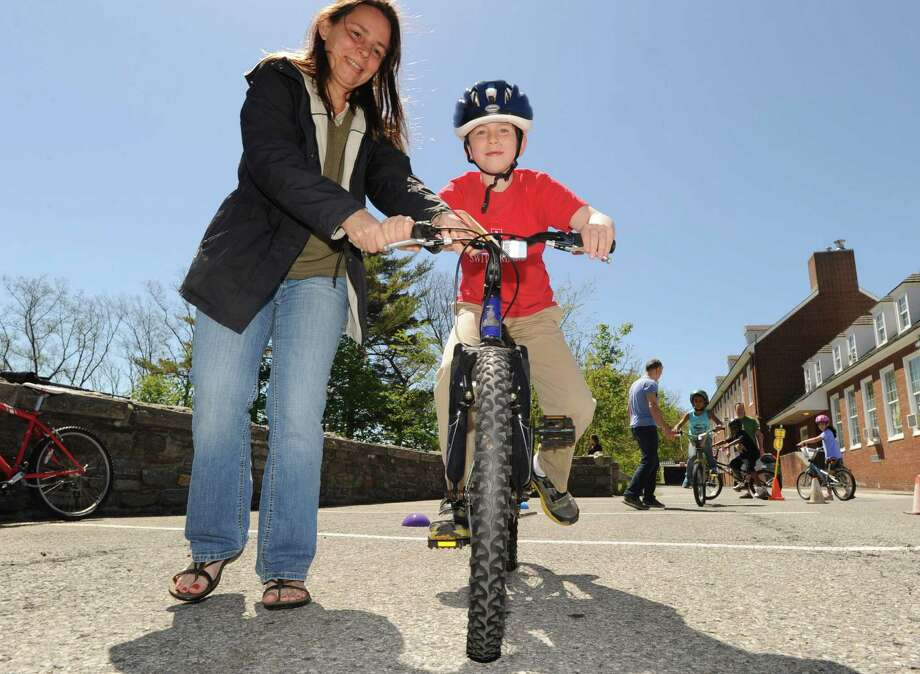 Kevin Toepelt, 7, of Greenwich, gets a little balancing help from his mom, Dawn, during the Bicycle Rodeo at the Julian Curtiss School in Greenwich, Saturday, May 4, 2013. The event, held  as part of National Bike Month to promote bicycle safety and the health benefits of biking, was sponsored by the Julian Curtiss School P.T.A, the YMCA of Greenwich, Greenwich Safe Cycling, and the Greenwich Police Silver Shield Association. Jamie Cahill of the Julian Curtiss School P.T.A. said more than sixty children attended the event. Photo: Bob Luckey / Greenwich Time