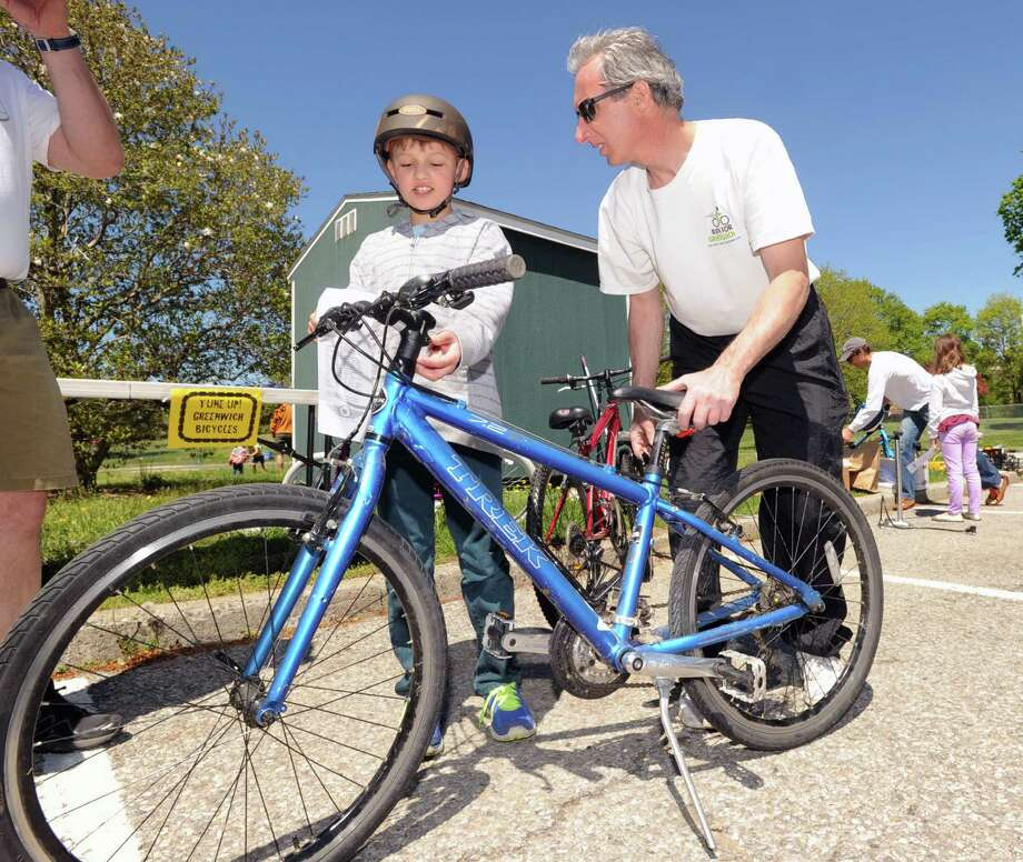 At left, Victor Stroie, 9, of Greenwich, has his bike's seat adjusted by Vin DeMarco of Greenwich Safe Cycling during the Bicycle Rodeo at the Julian Curtiss School in Greenwich, Saturday, May 4, 2013. The event, held  as part of National Bike Month to promote bicycle safety and the health benefits of biking, was sponsored by the Julian Curtiss School P.T.A, the YMCA of Greenwich, Greenwich Safe Cycling, and the Greenwich Police Silver Shield Association. Jamie Cahill of the Julian Curtiss School P.T.A. said more than sixty children attended the event. Photo: Bob Luckey / Greenwich Time