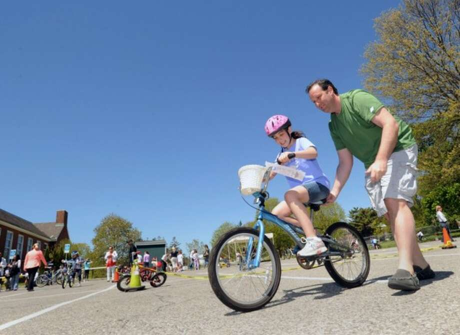 """Once you get it going, keep it going,"" said Greenwich resident Lance Porigow, right, while teaching his daughter, Sophie, 9, how to ride a bike during the Bicycle Rodeo at the Julian Curtiss School in Greenwich, Saturday, May 4, 2013. The event, held as part of National Bike Month to promote bicycle safety and the health benefits of biking, was sponsored by the Julian Curtiss School P.T.A., the YMCA of Greenwich, Greenwich Safe Cycling, and the Greenwich Police Silver Shield Association. Jamie Cahill of the Julian Curtiss School P.T.A. said more than sixty children attended the event."