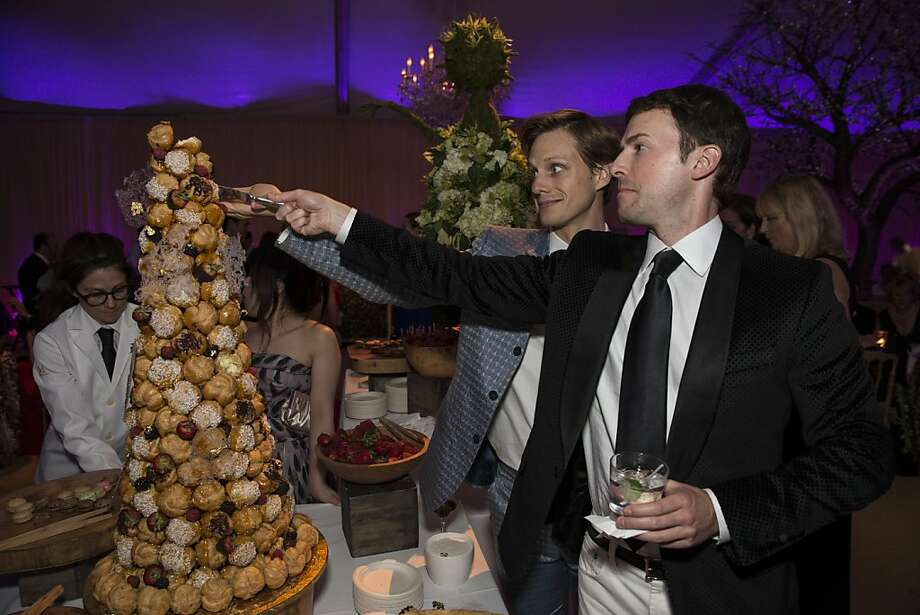 Luke Willis and Justin McBaine (right) try to cut off some dessert during the after party at the San Francisco Ballet's Cinderella Opening Night Ball in a tent outside War Memorial Opera House in San Francisco, Calif., on Friday, May 3, 2013.  The party celebrated the opening night and United States premiere of choreographer Christopher Wheeldon's production of Cinderella. Photo: Laura Morton, Special To The Chronicle