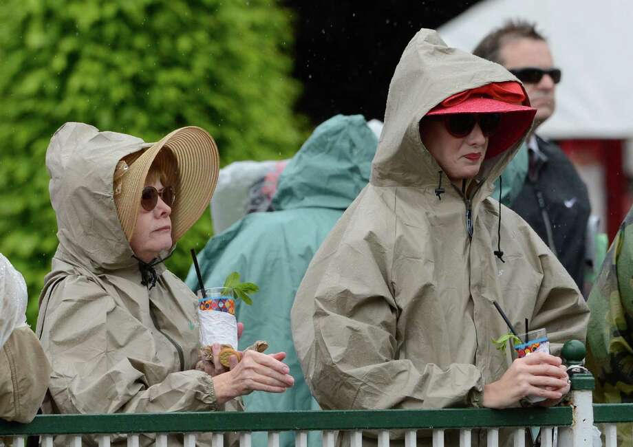 Stalwart racing fans tough out the rain to have their Kentucky Derby Experience including their mint juleps at Churchill Downs May 4, 2013 in Louisville, Kentucky.    (Skip Dickstein/Times Union) Photo: SKIP DICKSTEIN