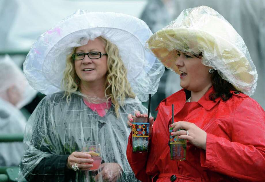 Stalwart racing fans, Michelle Schoengard, left and Kelly Johnson both of Louisville tough out the rain to have their Kentucky Derby Experience including their mint juleps at Churchill Downs May 4, 2013 in Louisville, Kentucky.    (Skip Dickstein/Times Union) Photo: SKIP DICKSTEIN