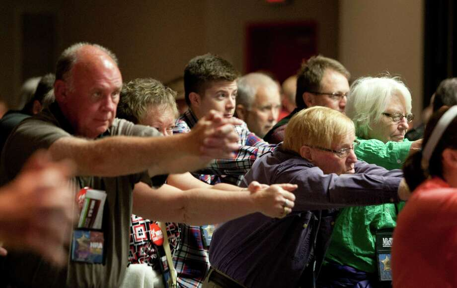 NRA attendees practice how to hold a firearm while listening to speaker Rob Pincus during the Defensive Shooting Skills Development seminar at the National Rifle Association's 142 Annual Meetings and Exhibits in the George R. Brown Convention Center Friday, May 3, 2013, in Houston. Photo: Johnny Hanson, Houston Chronicle / © 2013  Houston Chronicle