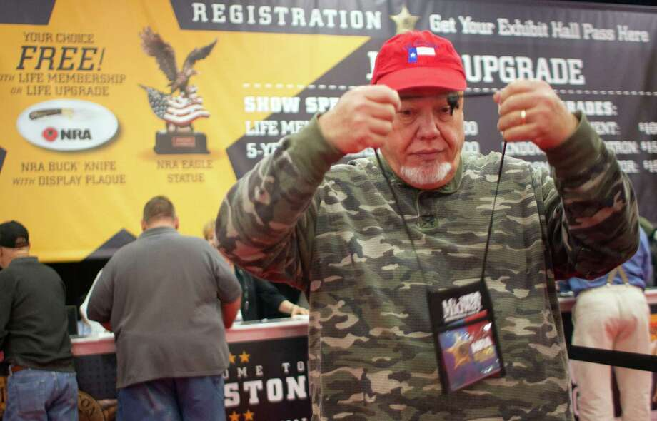 New NRA member Patrick Lindquist, of Meadows Place, puts on his NRA badge after registering for the National Rifle Association's 142 Annual Meetings and Exhibits in the George R. Brown Convention Center Friday, May 3, 2013, in Houston. Photo: Johnny Hanson, Houston Chronicle / © 2013  Houston Chronicle