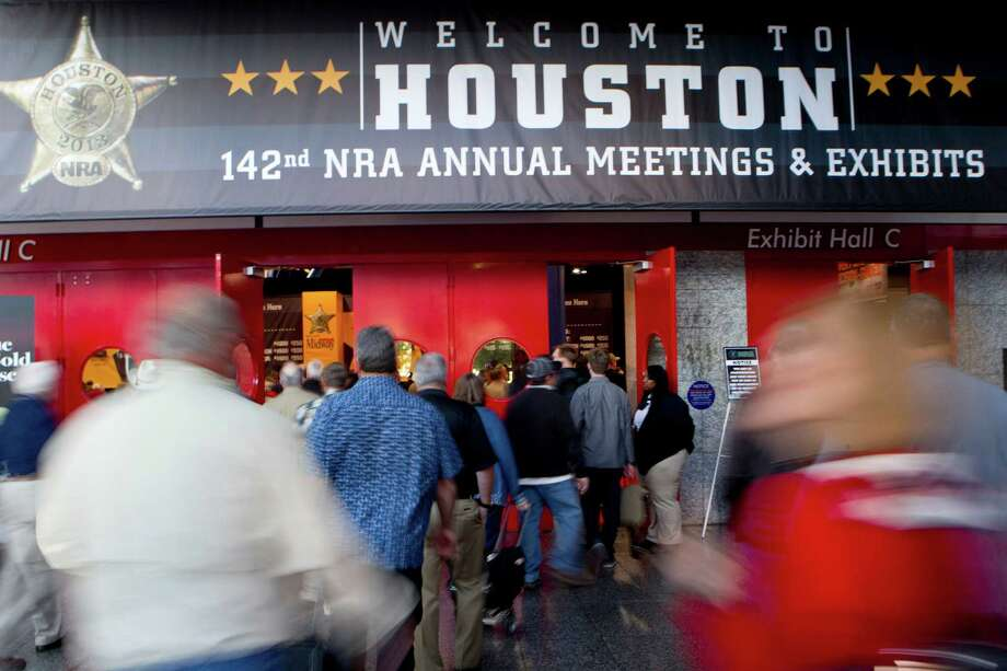 Attendees make their way into the opening of the National Rifle Association's 142 Annual Meetings and Exhibits in the George R. Brown Convention Center Friday, May 3, 2013, in Houston. Photo: Johnny Hanson, Houston Chronicle / © 2013  Houston Chronicle