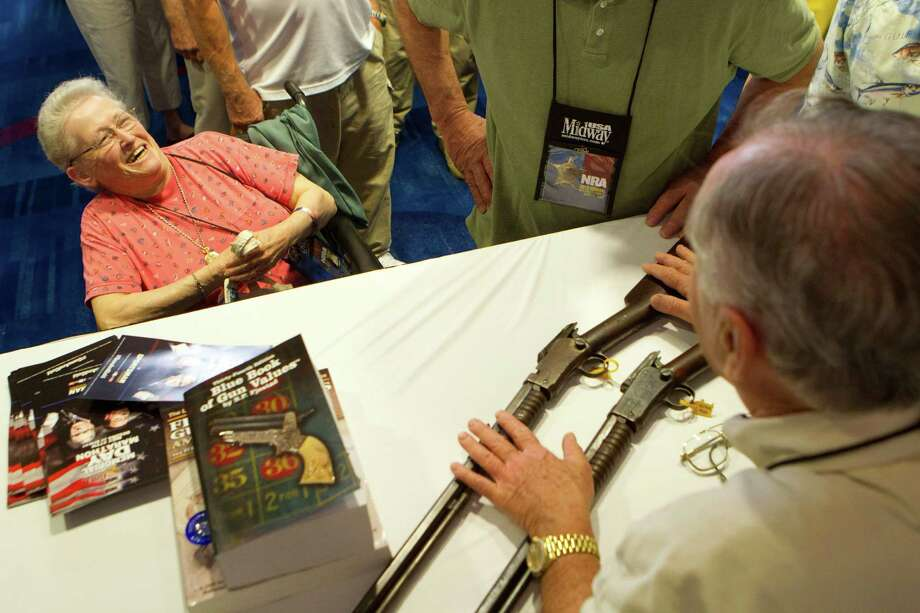 NRA attendee Janet Bero, of Newark, Ohio, has her Winchester rifles appraised during the NRA's Antiques Guns and Gold Showcase during the National Rifle Association's 142 Annual Meetings and Exhibits at the George R. Brown Convention Center Thursday, May 2, 2013, in Houston. 