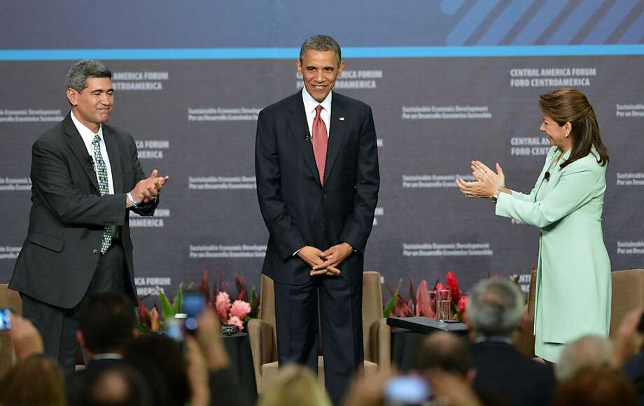 President Obama, flanked by INCAE University President Arturo Condo (left) and Costa Rica President Laura Chinchilla, is applauded after his speech emphasizing economic ties and trade. Photo: Rodrigo Arangua, AFP/Getty Images