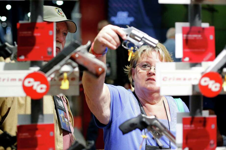 Expo attendees test out a set of revolvers on display, during day 1 of the 142nd NRA annual meetings and exhibits, Friday, May 3, 2013 at the George R Brown convention center in  (TODD SPOTH FOR THE CHRONICLE) Photo: © TODD SPOTH, 2013 / © TODD SPOTH, 2013