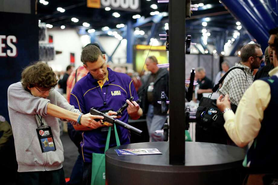 14-year-old Dylan Vidrine, left, and father, Ferral, inspect gun silencers at a booth, during day 1 of the 142nd NRA annual meetings and exhibits, Friday, May 3, 2013 at the George R Brown convention center in  (TODD SPOTH FOR THE CHRONICLE) Photo: © TODD SPOTH, 2013 / © TODD SPOTH, 2013