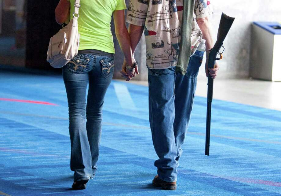Barry Bailey and his wife Judy, of DeRidder La., walk out hand-in-hand, after having their 1873 Winchester shotgun appraised at the NRA's Antiques Guns and Gold Showcase during the National Rifle Association's 142 Annual Meetings and Exhibits at the George R. Brown Convention Center Thursday, May 2, 2013, in Houston. 
