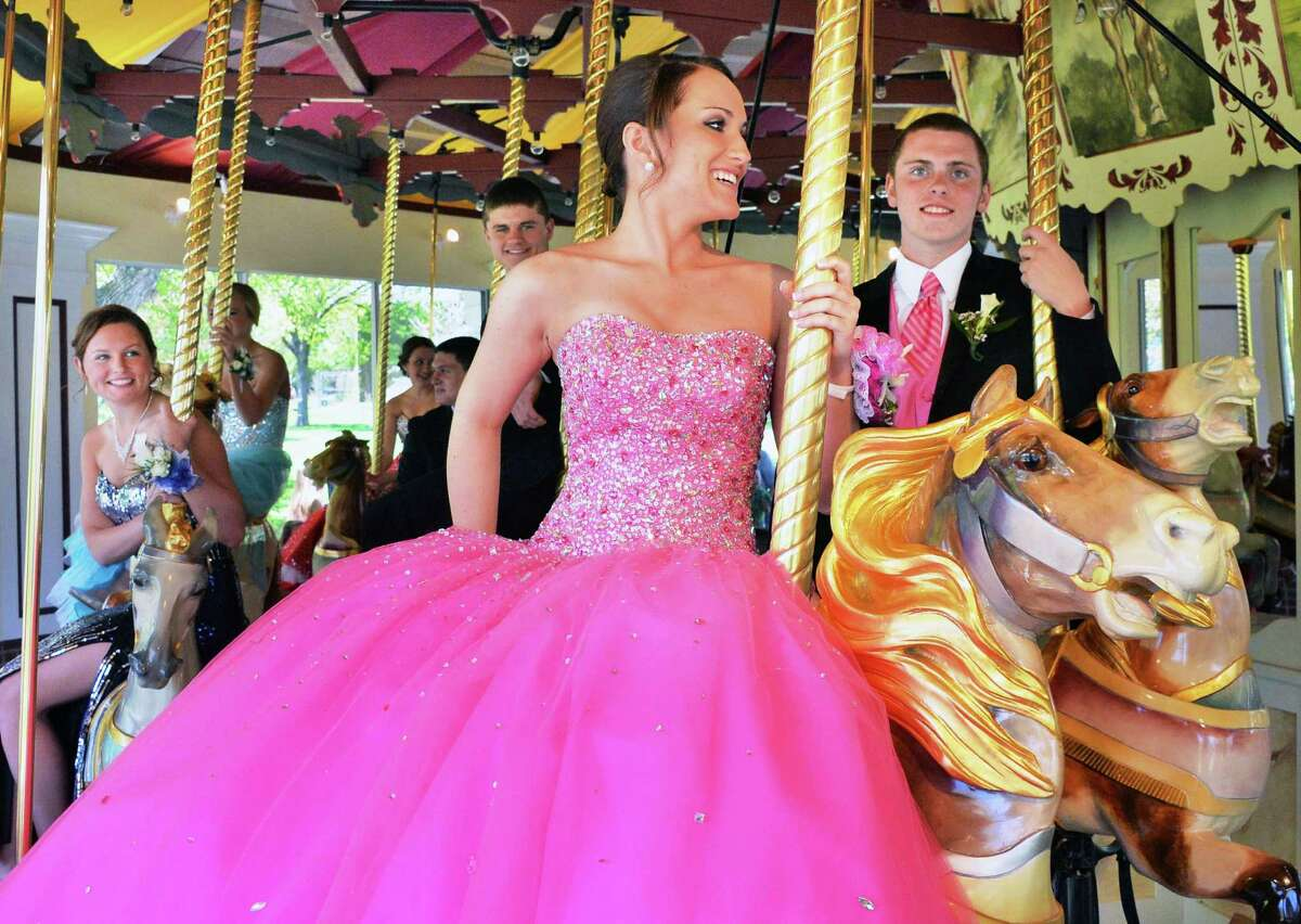 Dressed for their prom, South Glens Falls students Jamie Daley,17, left, and Kyle Bidwell, 17, ride on the Congress Park Carousel as it opens for the season in Saratoga Springs, NY Saturday, May 4, 2013. (John Carl D'Annibale / Times Union)