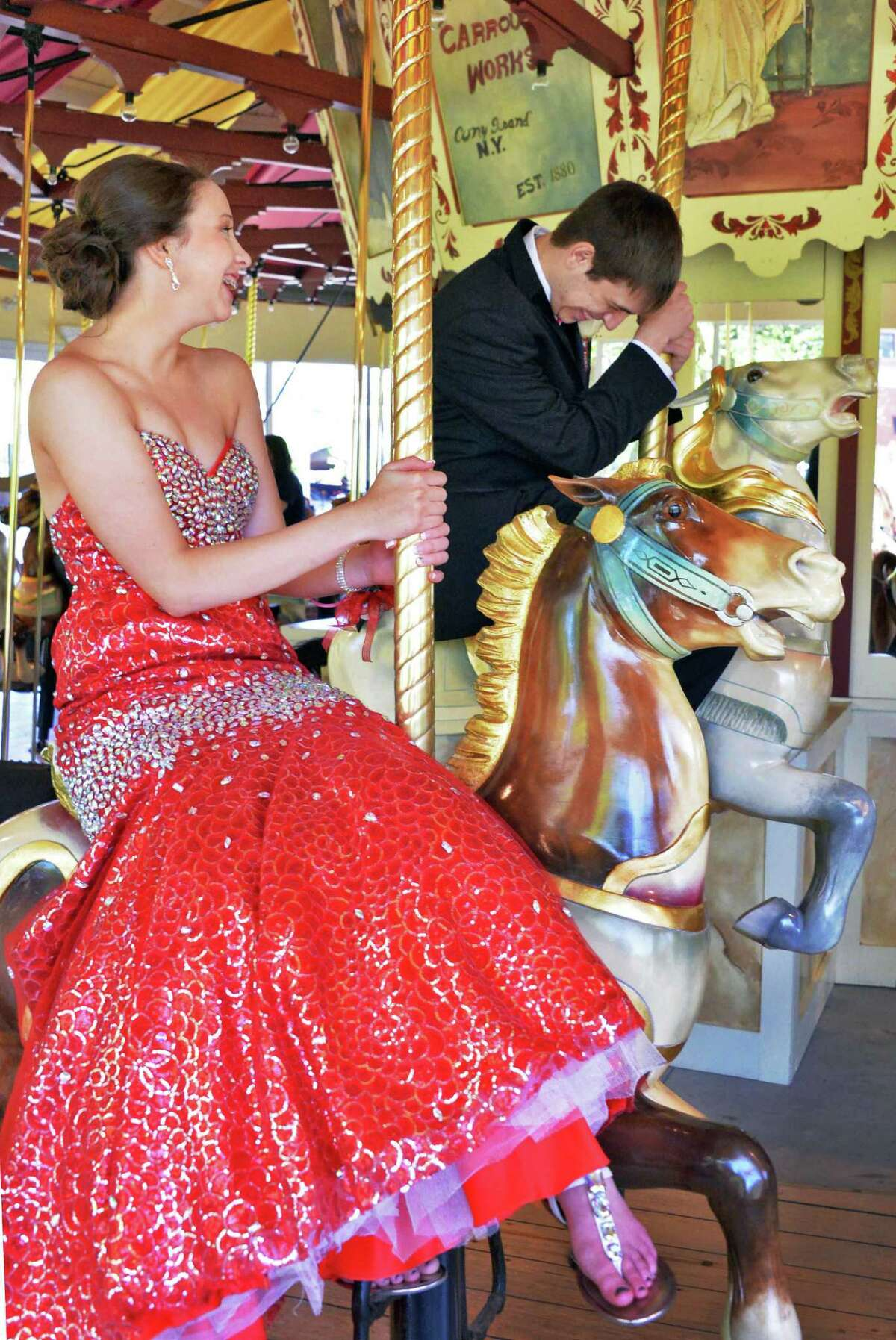 Dressed for their prom, South Glens Falls students Liz Raffile, 16, left, and Travis Rowe, 16, ride on the Congress Park Carousel as it opens for the season in Saratoga Springs, NY Saturday, May 4, 2013. (John Carl D'Annibale / Times Union)