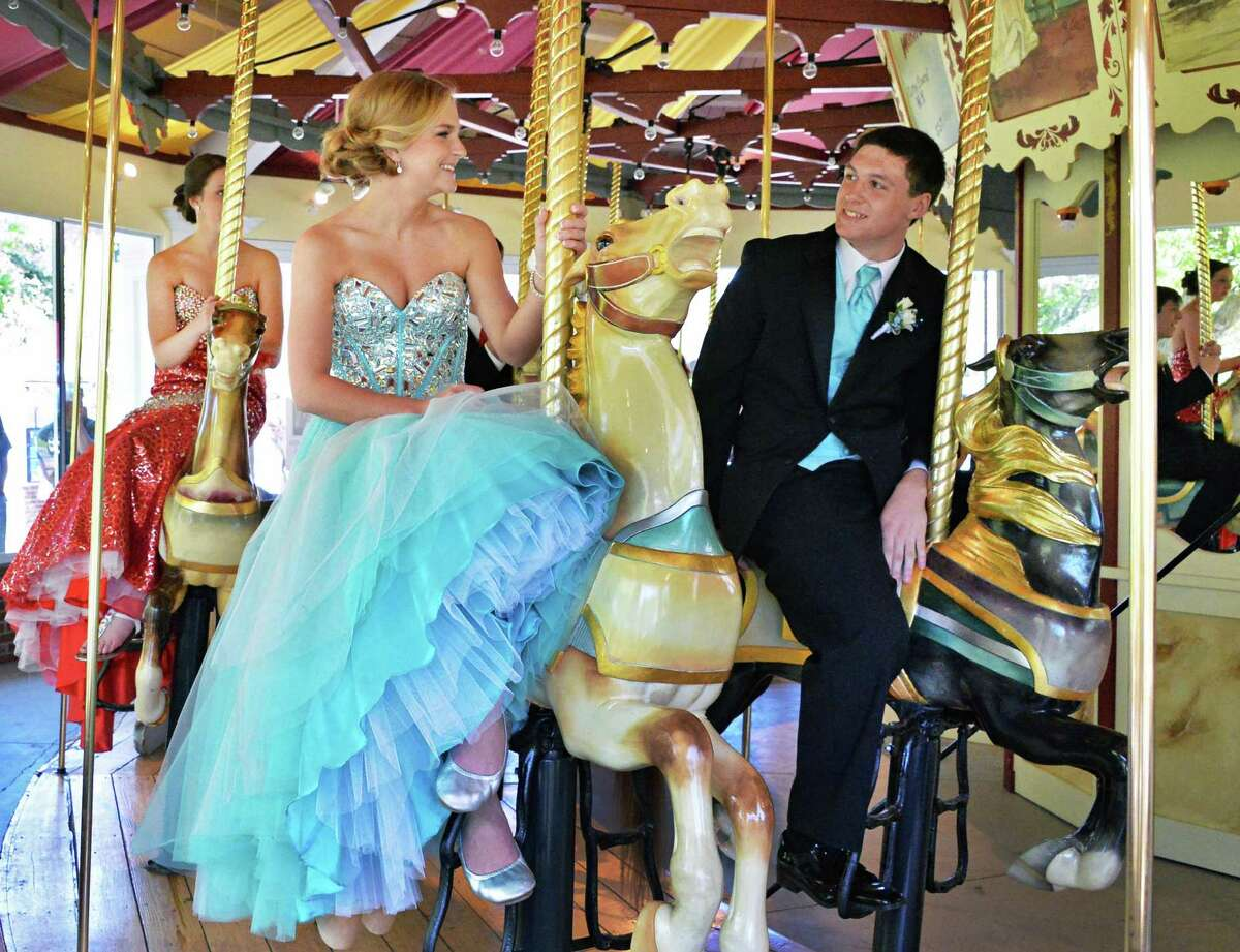 Dressed for their prom, South Glens Falls students Cadigan McNeary, 17, left, and Nolin Huntley, 15, ride on the Congress Park Carousel as it opens for the season in Saratoga Springs, NY Saturday, May 4, 2013. (John Carl D'Annibale / Times Union)