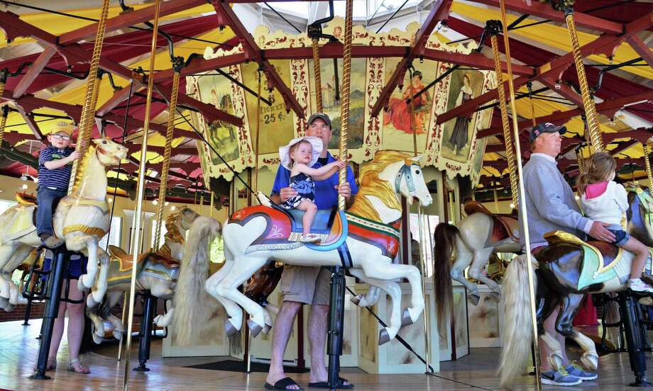 Chris Ward, center, of Saratoga Springs takes his 20-month-old daughter Adeline for a ride on the Congress Park Carousel as it opens for the season in Saratoga Springs, NY Saturday, May 4, 2013. The carousel will be open on weekends until June 21, after that, it will be open seven days a week until Labor Day. (John Carl D'Annibale / Times Union) Photo: John Carl D'Annibale / 10022188A